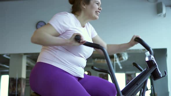 Thumbnail for Fat Woman Intensely Exercising on Stationary Bike