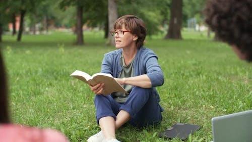 Teacher Reading to Pupils Outdoors