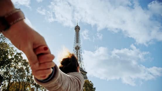 Thumbnail for POV View Travel Concept. Young Couple Holding Hands Woman Leading Boyfriend Walking Towards Eiffel
