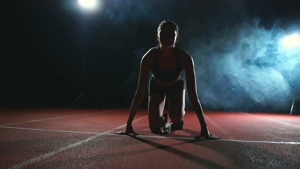 Thumbnail for Athlete Woman in Black Shorts and a T-shirt in Sneakers Are in the Running Pads on the Track of the
