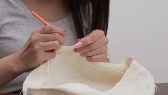 Thumbnail for Woman knitter making fabric from thread at home
