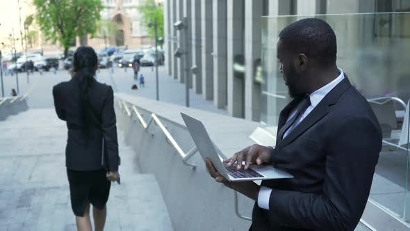 Cover Image for Man Working with Laptop Outside Office Giving Judgmental Look to Female Passerby