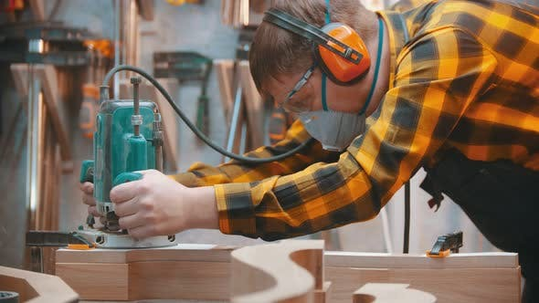 Thumbnail for Man Woodworker Polishes a Wooden Plank