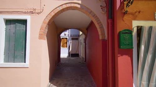 Short Arch Walkway Between Old Houses with Cobbled Road