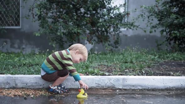 Vacation Kids, Little Boy Have Fun Playing Rubber Duck for Swimming in Puddle