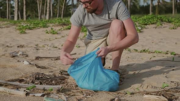 Mann holt Abfall auf den Strand geworfen
