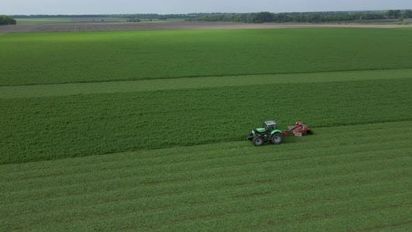 Mowing with a Agriculture Machine Modern Tractor with Mowers on the Big Farm Field