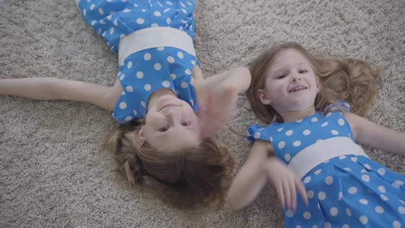 Thumbnail for Top View of Cute Little Caucasian Girls Waving at Camera and Smiling. Joyful Brunette Twin Sisters