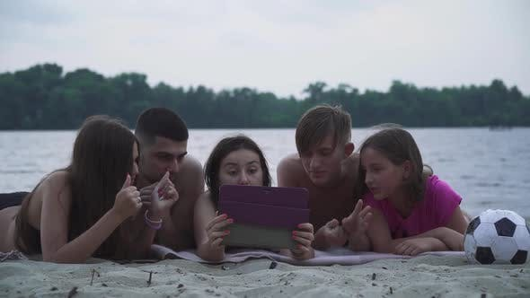 Thumbnail for Beautiful Young People Lie with a Tablet on the Beach By the River