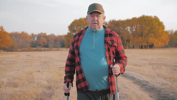 Senior Man Doing a Nordic Walk on a Sunny Day