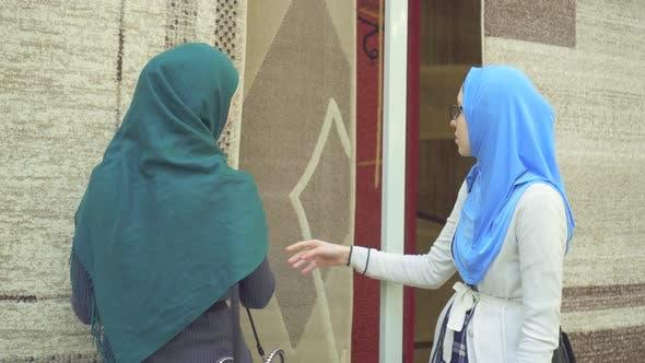 Two Young Muslim Women in Hijabs Choose Carpet
