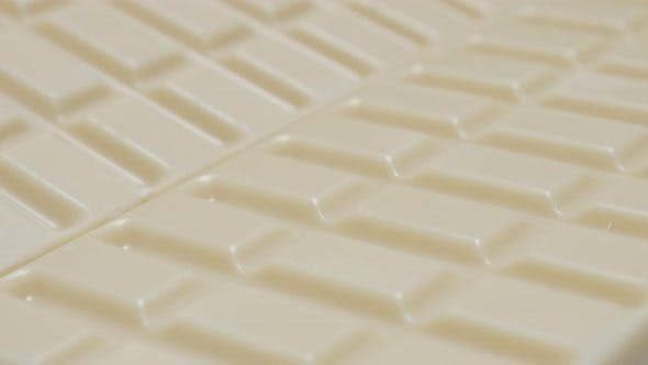 Thumbnail for Shiny white milk chocolate blocks in the row slow tilt 4K 2160p 30fps UltraHD video - Tilting over s