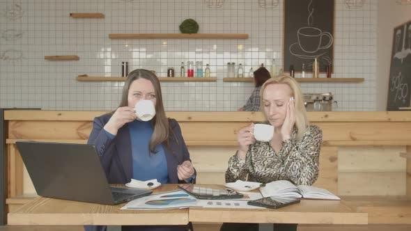 Businesswomen Drinking Coffee Talking in Cafeteria