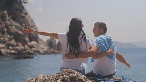 Romantic couple sit and embrace near the sea. Man and woman with black hair spend vacation