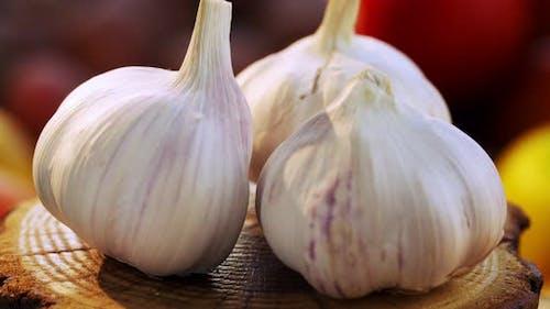 Whole garlic bulbs in the peel rotate around an axis