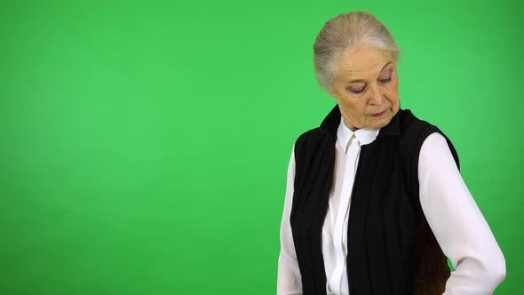 Thumbnail for An elderly woman adjusts her clothes and smiles at the camera - green screen studio