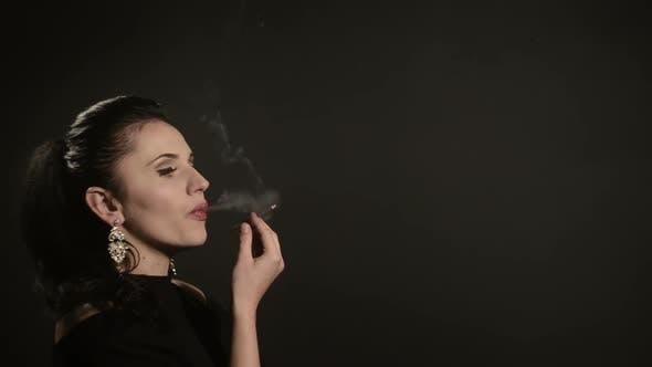 Beautiful Woman Smokes a Cigarette on a Black Background