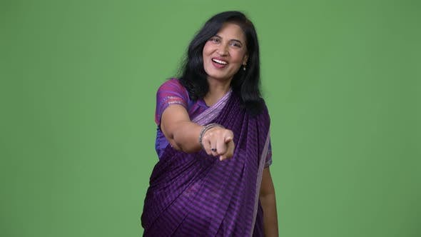 Thumbnail for Mature Happy Beautiful Indian Woman Pointing at Camera While Wearing Sari Traditional Clothes