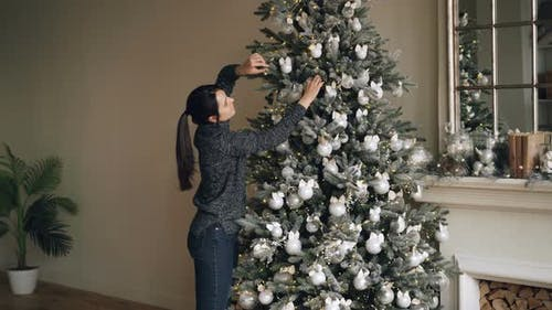 Good-looking Brunette Is Decorating Fir-tree with Beautiful Balls and Lights Enjoying Festive
