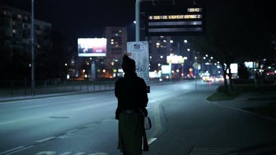 Woman Waiting for Bus at the Bus Stop at Night