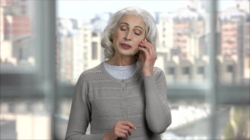Old Lady Calling and Talking on Transparent Phone with Copy Space
