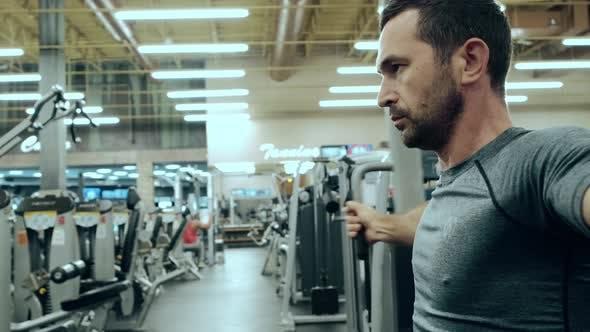 Modernes Fitnessstudio ein Mann sitzt auf dem Trainingsgerät und Training
