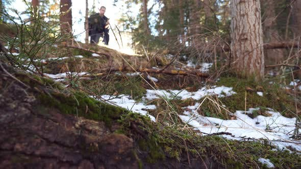 Thumbnail for Guy Walks Down on Slope of Pine Forest with Bright Sunlight at Background. Young Hiker Goes Down the