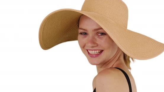 Thumbnail for Cute millennial woman wearing floppy sunhat and smiling on white background