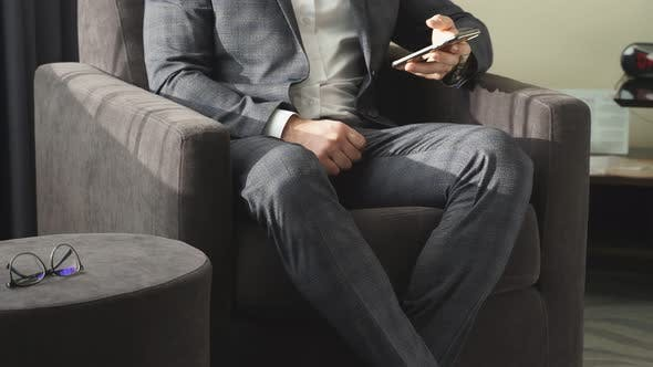 Business Man with Mobile Phone Sitting on Couch