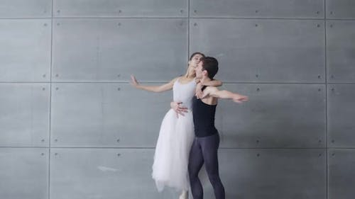 Elegant Couple of Classical Ballet Dancers Rehearsing a Dance on a Gray Background Romantic Dance of