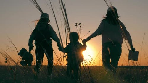 Mother and Two Children Walking in the Meadow at the Sunset Time. Silhouette Happy Beautiful Family