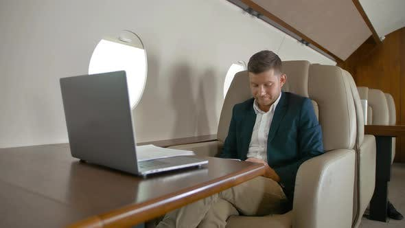 Businessman Chatting Sitting in Comfortable Armchair in Private Jet Cabin