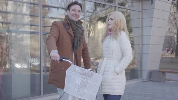 Thumbnail for Tall Man Holding His Bicycle Talking with Blond Woman in Warm Jacket