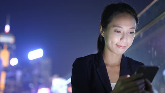 Cover Image for Businesswoman use of cellphone in Hong Kong city