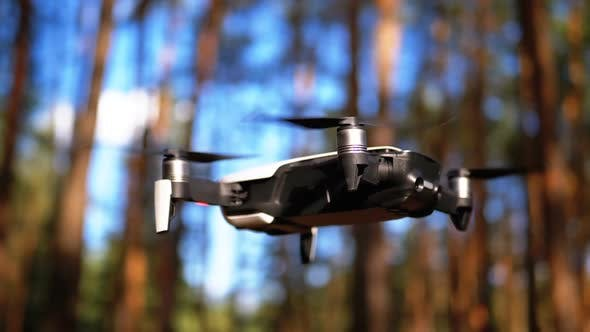 Thumbnail for Drone with a Camera Hovers in the Air Above the Ground in the Forest. Slow Motion.
