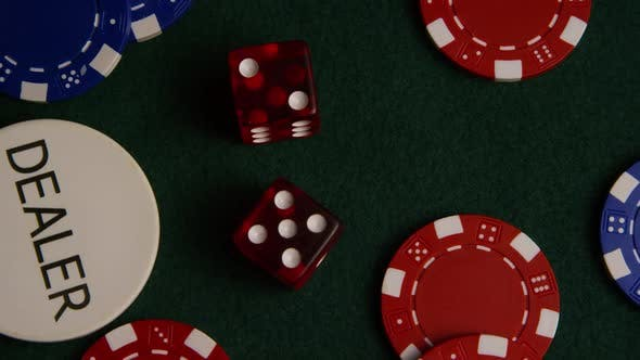Rotating shot of poker cards and poker chips on a green felt surface - POKER 025