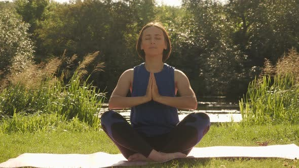 Beautiful woman practicing yoga in summer park at sunrise. Meditation in the morning.