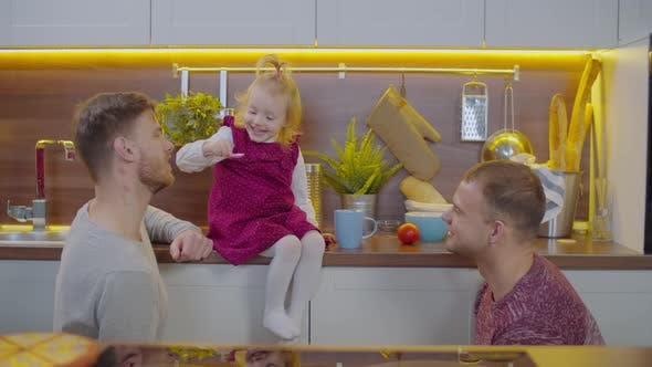 Excited Baby Feeding Joyful Gay Parents in Kitchen