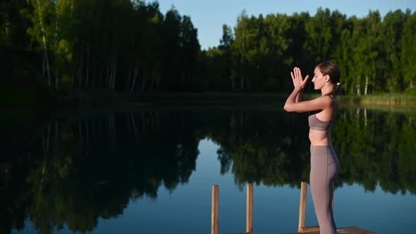 Young Woman Practicing Yoga on the Wooden Berth at Lake. Single Sport Healthy Training on Nature at