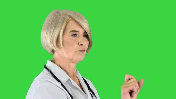 Healthcare Medicine and Technology Concept Senior Female Doctor Pointing To Something or Pressing