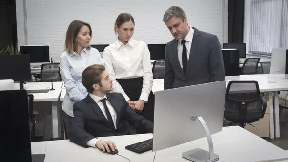 Thumbnail for Corporate Business Team Discussing Project in front of Computer