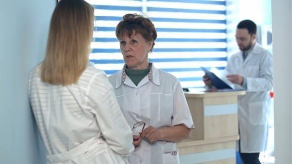 Two nurses talking near reception desk