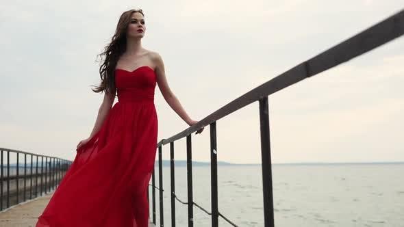 Slim Fashion Model Dressed in Long Silk Dress is Posing on a Pier in Daytime