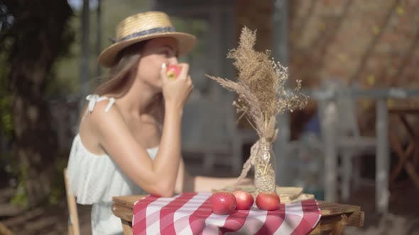 Thumbnail for Young Rural Girl in a Straw Hat and White Dress Sitting at the Small Table with Vase with Decorative