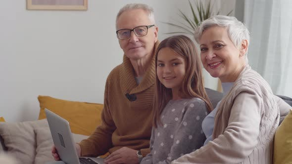 Thumbnail for Grandparents and Granddaughter with PC on Sofa