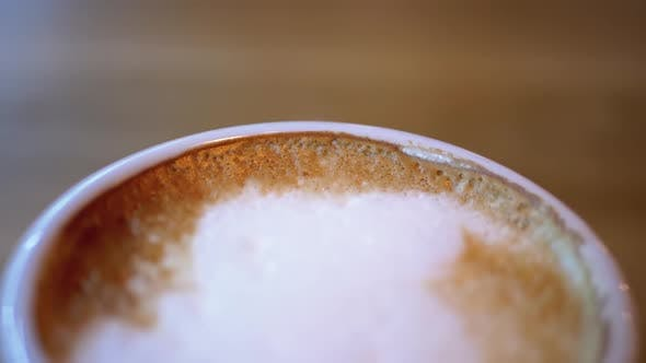 Thumbnail for Cup of Cappuccino with White Foam on the Wooden Table in the Restaurant. Close-up
