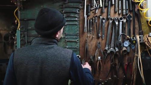 Man Taking Wrench at Garage