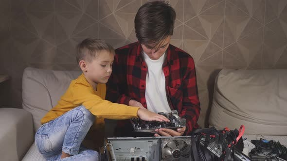 Thumbnail for Teenager Has Removed the Motherboard From the Computer and Is Looking at It with His Younger Brother