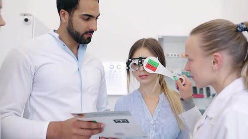Eye Exam. Doctors Checking Woman Eyesight With Optometry Glasses