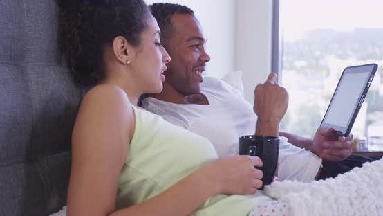 Thumbnail for Happy loving multi-ethnic couple sitting up in bed using tablet computer drinking coffee Handheld sh